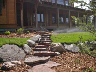 Stone slab steps and moss rock boulders give a natural look to this front entry in Big Sky.
