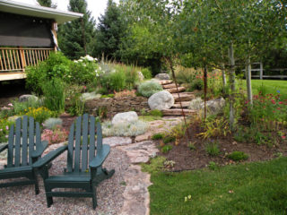 Pea gravel sitting area with flagstone border and steps accent this perennial garden Bozeman's south side.