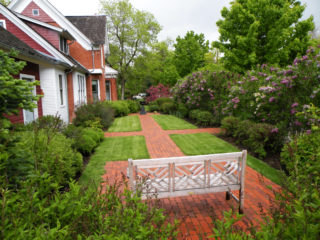 This private garden is surrounded with maturing shrubbery and features a brick walkway and patio.