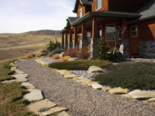 Pea gravel path with sandstone edging compliment this xeriscape in Gallatin River Ranch.