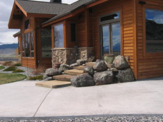 Moss rock boulders and stone slabs create functional access to the patio.