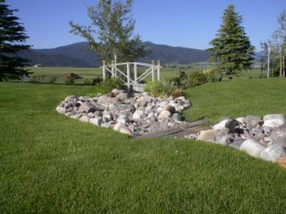 A dry creek bed helps carry runoff water away from the house.  The creek is bridged by a stone slab to allow mower access.